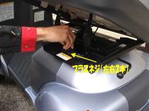 シートを90度回転させ、バッテリーカバー固定ネジ(鉄製・左右1本ずつ)を取り外します。