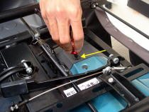 シートを90度回転させ、バッテリーカバー固定ネジ(プラスチック製・左右1本ずつ)を取り外します。